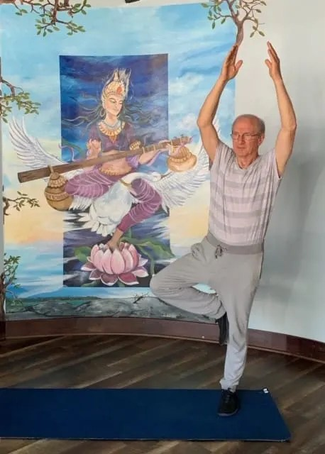 Jerry Eisner standing on one leg in front of yoga themed background