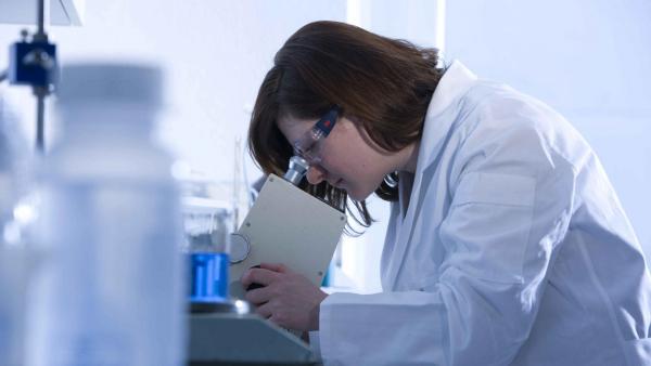 Frau schaut in ein Mikroskop