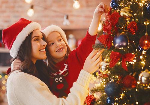 Mutter & Tochter dekorieren den Weihnachtsbaum