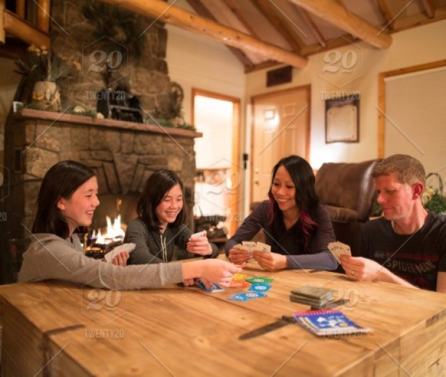 Enjoying A Warm Fire And Family Game Night In A Winter Cabin