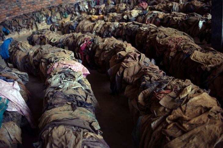 The clothes of victims killed during the Rwandan genocide are laid out on benches