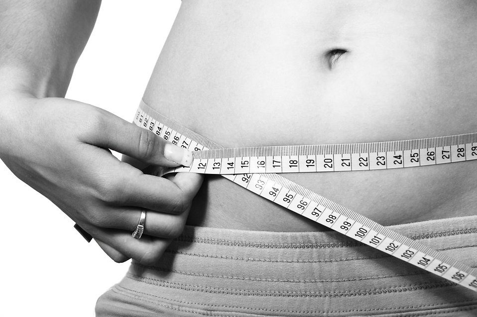 A woman measuring her belly : Free Stock Photo