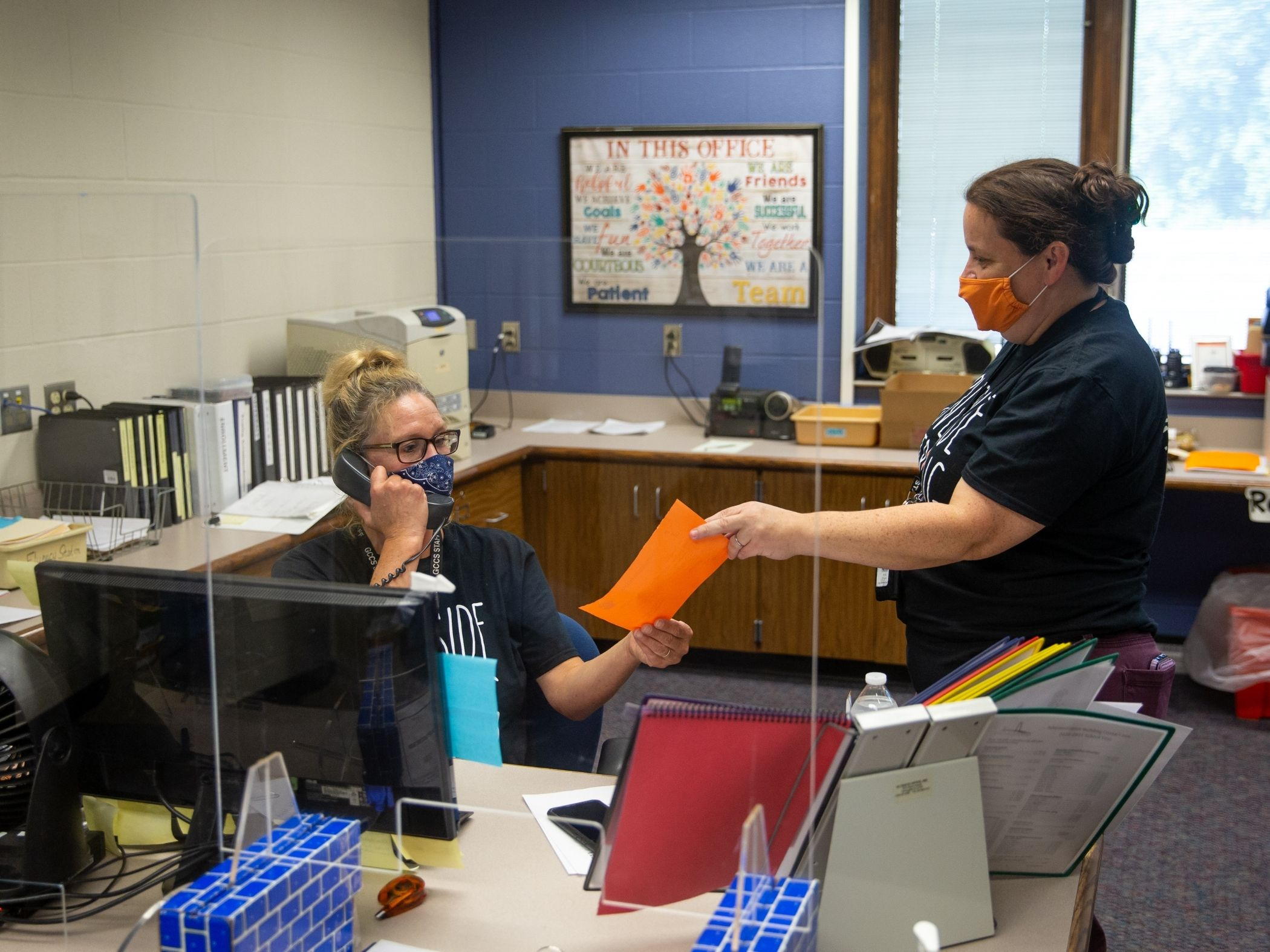 A staff member with an orange mask hands a piece of paper to seated office worker