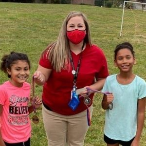 Riverside Elementary School Staff Member smiling with two students