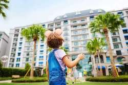 Young girl wearing Mickey Ears stares up at the entrance of a resort framed by palm trees.
