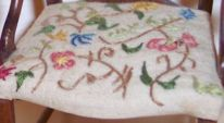 Detail of the hand-embroidered crewel embroidery on the fretwork chair.
