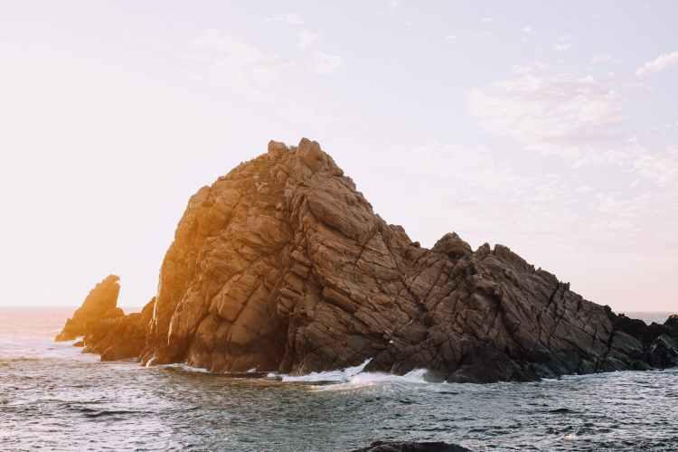 rocky cliff in rippling water of ocean in bright light