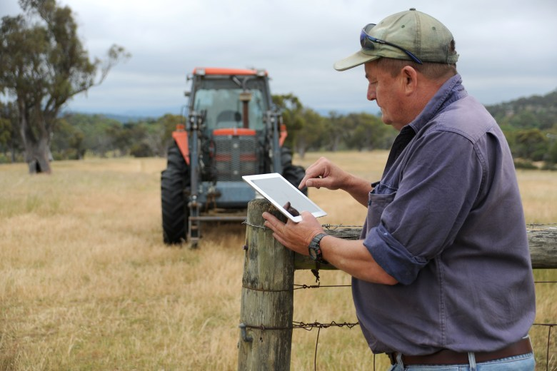 Farmer with tractor and ipad