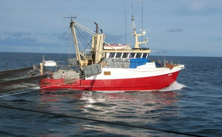 A red and white commercial fishing boat with trawl nets extended behind the vessel.