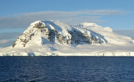 View of Antarctica - the ocean in foreground with mountain encases in snow in distance