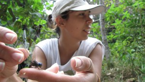 A woman holding a dangonfly gently on her finger.