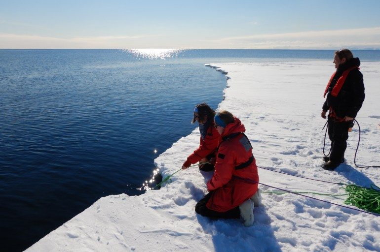Three woman on sea ice at the ocean's edge in Antarctica. Two are kneeling while holding a green rope that is going into the ocean and the third is standing.