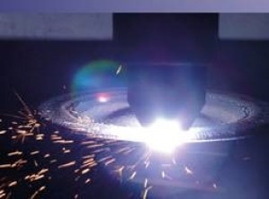 Plasma Transferred arc, laser is hitting metal surface causing sparks to fly to left of image