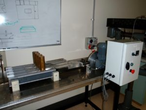 Miller tester. Bench top with metal device on top. Four metal slabs with cone like cylinders on each slab. Wires connected to adjasent machine with on/off button
