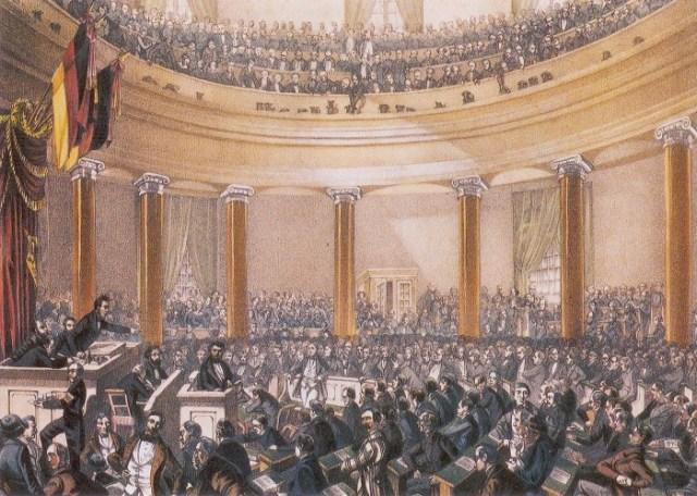 Le Parlement de Francfort  (Frankfurter Nationalversammlung) a siégé entre le 18 mai 1848 et le 31 mai 1849 dans l'église Saint-Paul de Francfort. Il s'agissait de la première assemblée élue en Allemagne. Elle a été créée à la suite de la révolution de mars qui secoua les États de la confédération germanique en 1848. Elle vote en décembre 1848 un catalogue de droits fondamentaux et en mars 1849 la constitution, qui prévoyait entre autres la garantie des droits fondamentaux et une monarchie constitutionnelle avec un empereur (Kaiser) héréditaire à sa tête. Le roi de Prusse Frédéric-Guillaume IV refusa la couronne impériale qui lui était proposée. Le travail de l'assemblée a servi de modèle pour la constitution de la république de Weimar en 1919 et pour celle de la RFA (capitale Bonn) en 1949. L'image montre une session en juin 1848 pendant un discours de Robert Blum, démocrate et républicain, exécuté, au mépris de son immunité parlementaire par les troupes contre-révolutionnaires autrichiennes à Vienne en octobre 1848.