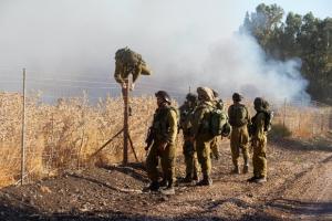 Des soldats israéliens inspectent un champ où sont tombées des roquettes tirées depuis la Syrie près de Kfar Szold au nord d'Israël, proche du Plateau du Golan et de la frontière libanaise, en août 2015 – Photo AFP