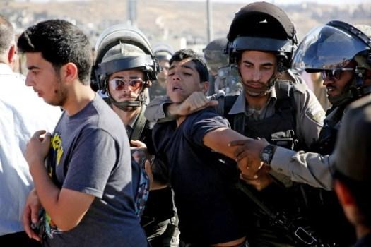 La police aux frontières israélienne arrête un jeune Palestinien alors qu'une foule se fraie un chemin à travers le poste de contrôle de Qalandia, en Cisjordanie occupée, pour assister aux prières du vendredi (AFP)