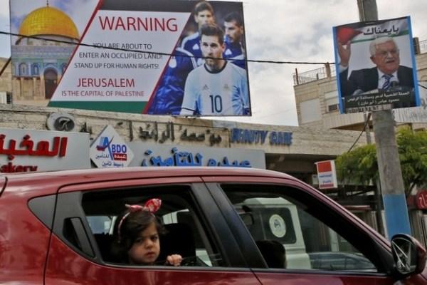 Une affiche dans la ville cisjordanienne d'Hébron dénonce l'occupation israélienne tout en appelant au boycott d'un match de football entre l'Argentine et Israël, le 5 juin 2018 (AFP)