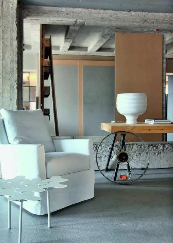Une table d'appoint « Nanook » imaginée par le designer Philippe Bestenheider pour la maison Moroso et un fauteuil blanc distribué par Casa Di Patsi font face au lit.