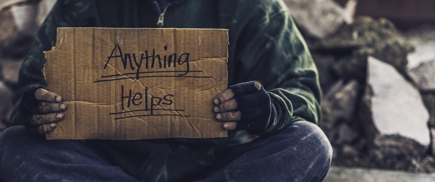 "Homeless person holding cardboard sign that says ""Anything Helps"""