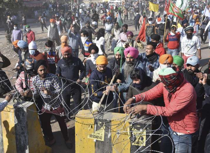 India Tv - New Delhi: Farmers attempt to cut concertina wire fencing at a police barricade as they march towards Delhi during Delhi Chalo protest march against the new farm laws, at Singhu border in New Delhi, Friday, Nov. 27, 2020.