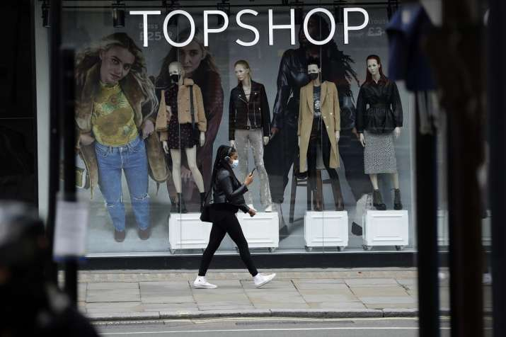 Woman wearing a face mask walks past mannequins wearing face masks in the window of a temporarily cl