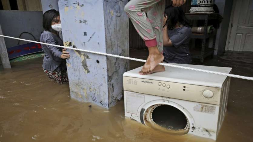 A girl looks on as she stands in the water at a flooded neighborhood following heavy rains in Jakarta, Indonesia.