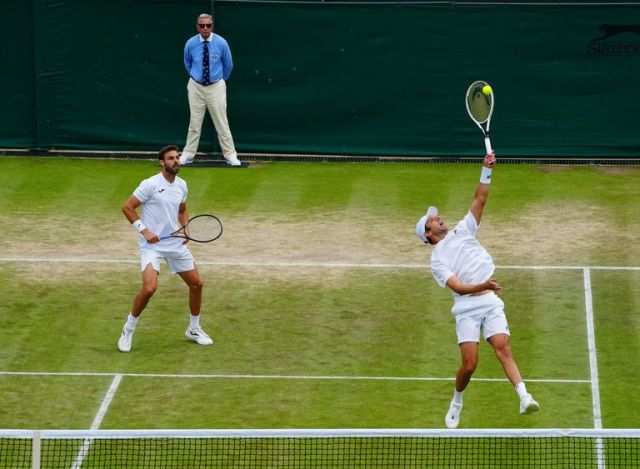 El marplatense Horacio Zeballos ejecuta un smash en la semifinal de Wimbledon que junto al español Marcel Granollers Pujol les ganó al italiano Simone Bolelli y al tandilense Máximo González.