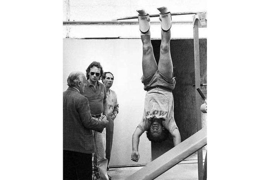 Diego, colgado patas para arriba, para trabajar sus dolores de ciática, con Signorini al lado.