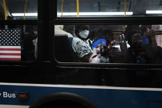 Pasajeros con barbijo a bordo de un ómnibus en Brooklyn, Nueva York