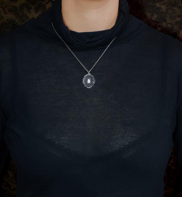 Petit collier scarabée noir egyptien dans cadre ovale baroque inspiré des cabinets de curiosités de fabrication artisanale porté | Res Mirum