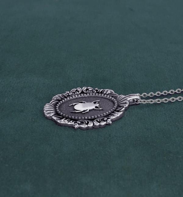 Petit collier scarabée noir egyptien dans cadre ovale baroque inspiré des cabinets de curiosités de fabrication artisanale vue côté | Res Mirum