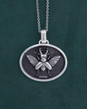 Pendentif scarabée lucane cerf-volant dans son cadre ovale en argent massif fabriqué artisanalement | Res Mirum