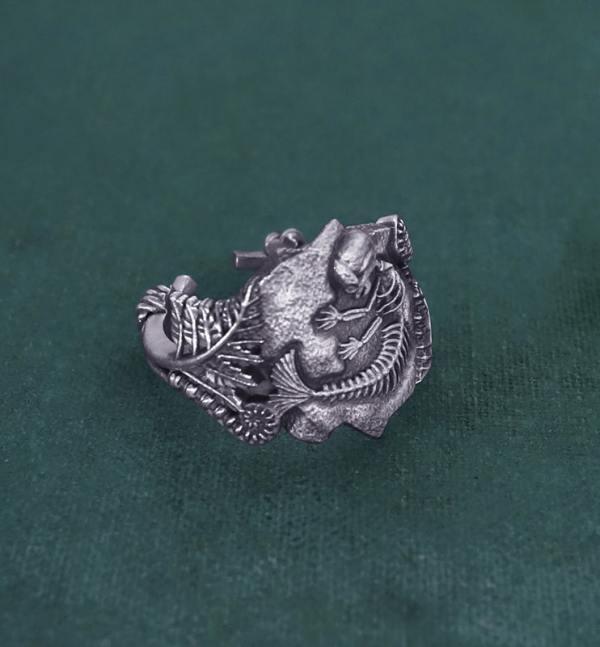 Bague ornée d'un fossile de foetus de sirène et de fougères, inspirée des chimères anciennes de la paléontologie en argent de fabrication artisanale vue côté gauche | Res Mirum
