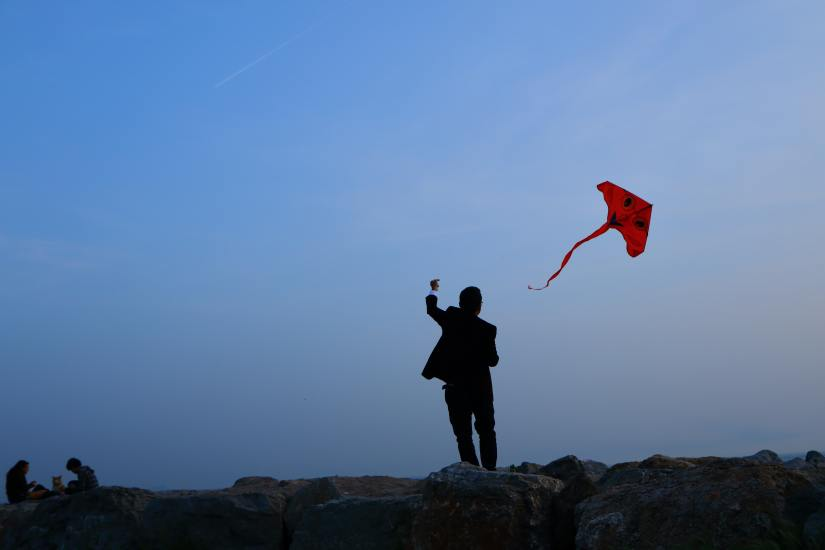 picture of man in a suit flying a kite