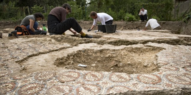 Archaeologists from Inrap (French National Institute for Preventive Archaeological Research) excavate mosaics at an archaeological site from the Gallo-Roman era, on July 11, 2017 in Auch. / AFP PHOTO / Eric CABANIS