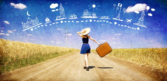 Lonely girl with suitcase at country road dreaming about travel.