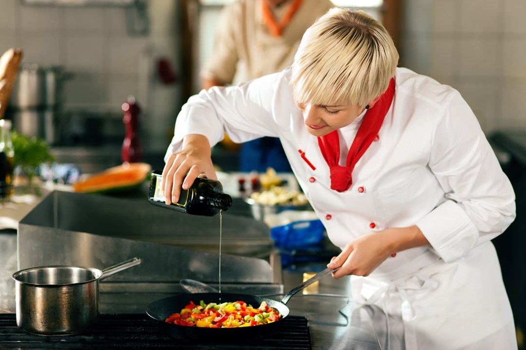 A chef working hard to prepare delicious food in a shared kitchen space.