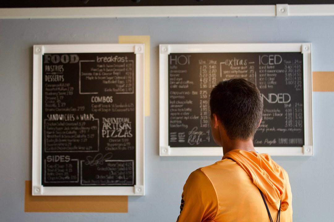 Man looking at menu posted