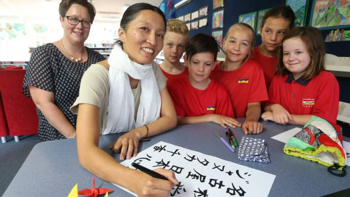 Witherlea School gala organiser Tash Stewart, left, and parent Chika Janutka, centre, practice Japanese characters with Year 5 pupils, from left, Connor Davies, LIam Walker, Jess Kelly, Shanaya McElhinney, and Aimee Stewart.