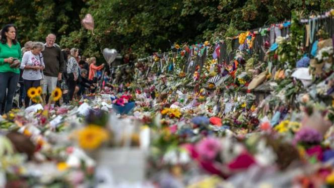 People view flowers and tributes left in Christchurch's Botanical Gardens.