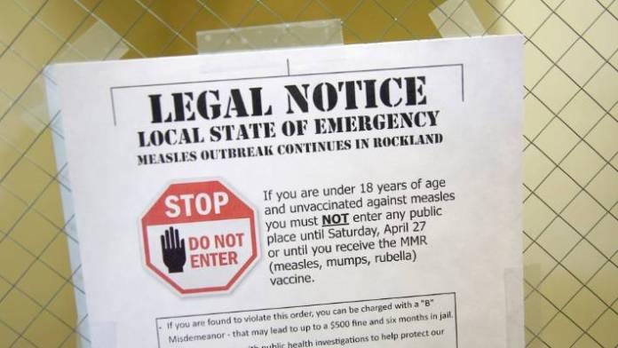 Ein Schild, das den örtlichen Ausnahmezustand wegen eines Masernausbruchs in der Rockland County Health Department in Pomona, New York, erklärt. Masern breiten sich durch die Luft aus, wenn eine infizierte Person hustet oder niest. Es ist so ansteckend, dass 90 Prozent der Menschen, die nicht immunisiert sind, infiziert sind, wenn sie dem Virus ausgesetzt sind, so die US-amerikanischen Zentren für Krankheitskontrolle und Prävention.