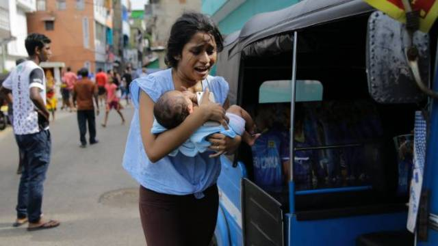 A Sri Lankan woman living near St. Anthony's shrine runs for safety with her infant after police found explosive devices in a parked vehicle in Colombo.