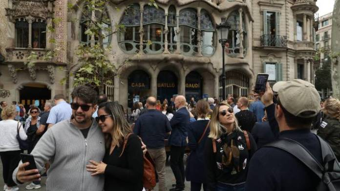 Tourists gather for snapshots and selfies in front of Casa Batllo, designed by Catalan architect Antoni Gaudi.