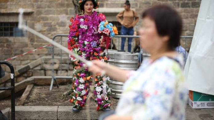 A street artist covered in paper flowers stands among tourists, including one with a selfie stick.