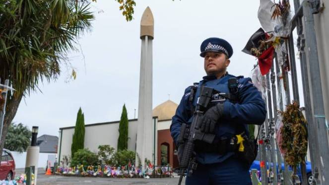 A police officer stands guard in front of Al Noor Mosque.