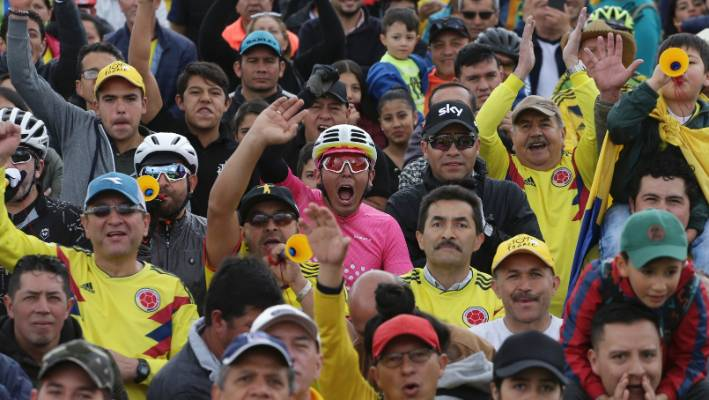 Colombian cycling supporters, watching the race on a big screen, cheer on Egan Bernal.