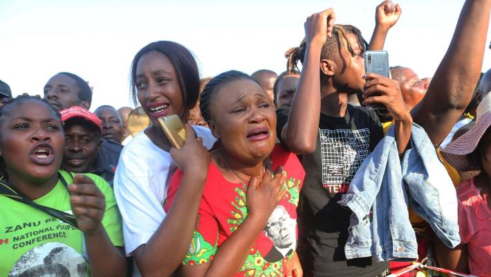 Supporters of Zimbabwe's former ruler, Robert Mugabe react upon the arrival of his remains at at RG Mugabe airport in Harare.