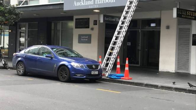 A ladder lies on the awning the morning after the woman fell to her death at the Auckland Habour Suites complex early on Sunday.