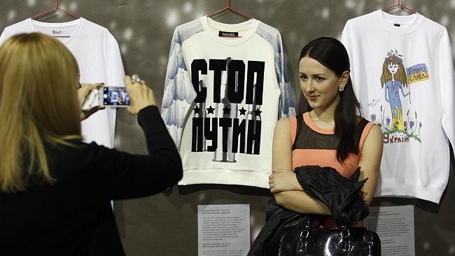 "Proactive ... A fashionista poses in front of T-shirts with the words ""Stop Putin"" and ""G"